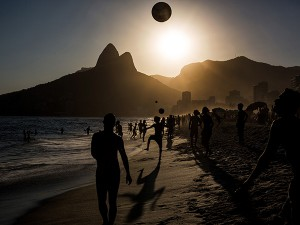 People playing soccer ball on Ipanema beach at sunset, Rio de Janeiro.